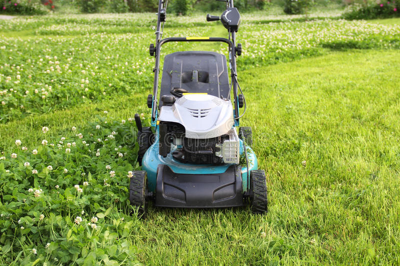 Lawn Mower. On fresh cut grass in the garden royalty free stock photography
