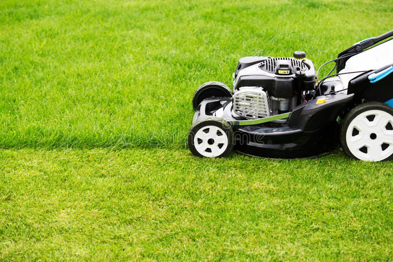 Lawn mower. In the garden royalty free stock image