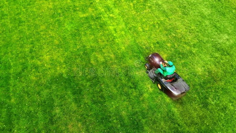 Lawn mower with gardener. Grass cutting. Aerial from drone. stock photography