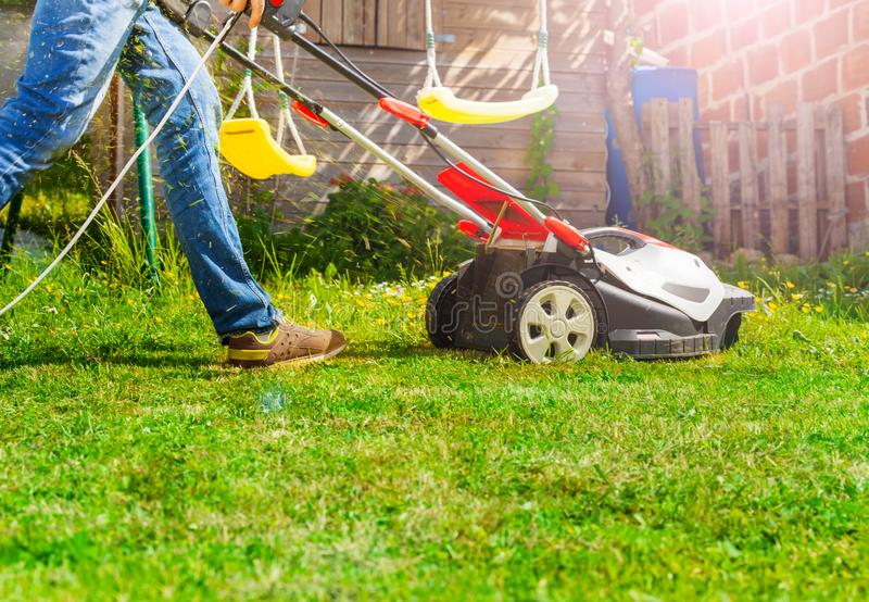 Lawn mower man using walk behind lawnmower stock photography