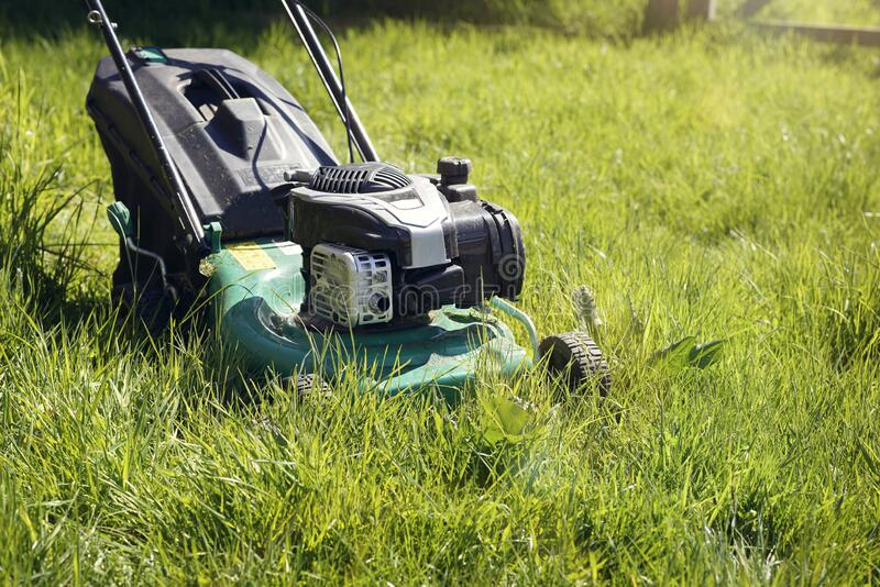 Lawn mower mowing the long grass stock photos
