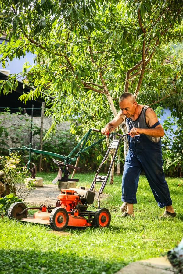 Lawn mowing - summer lawn mowing. Lawn mowing to cut a grass at my home. The farmer cuts grass in the yard stock images