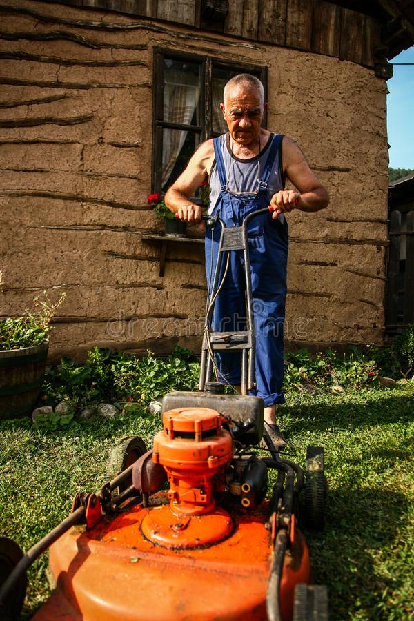 Lawn mowing - summer lawn mowing. Lawn mowing to cut a grass at my home. The farmer cuts grass in the yard stock image