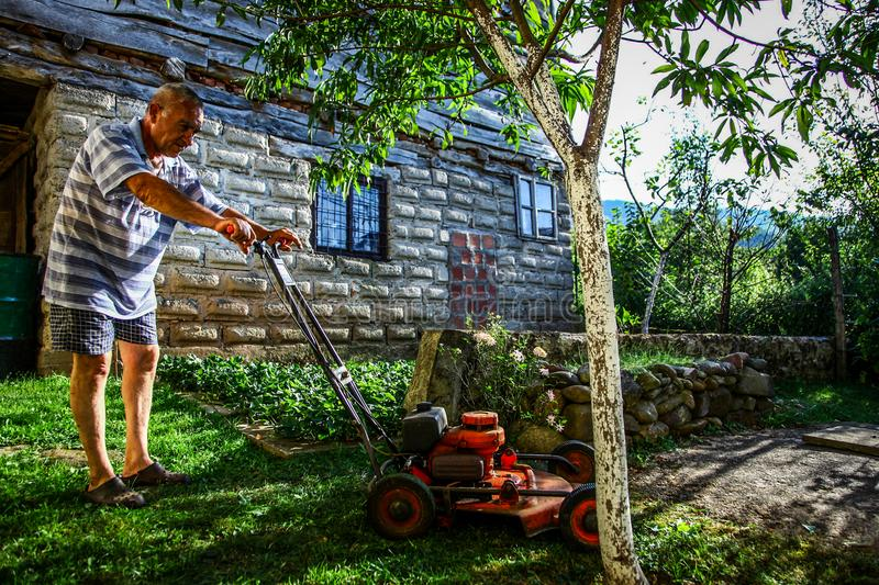 Lawn mowing - summer lawn mowing. Lawn mowing to cut a grass at my home. The farmer cuts grass in the yard royalty free stock image