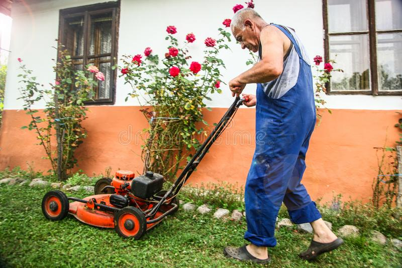 Lawn mowing - summer lawn mowing. Lawn mowing to cut a grass at my home. The farmer cuts grass in the yard royalty free stock images