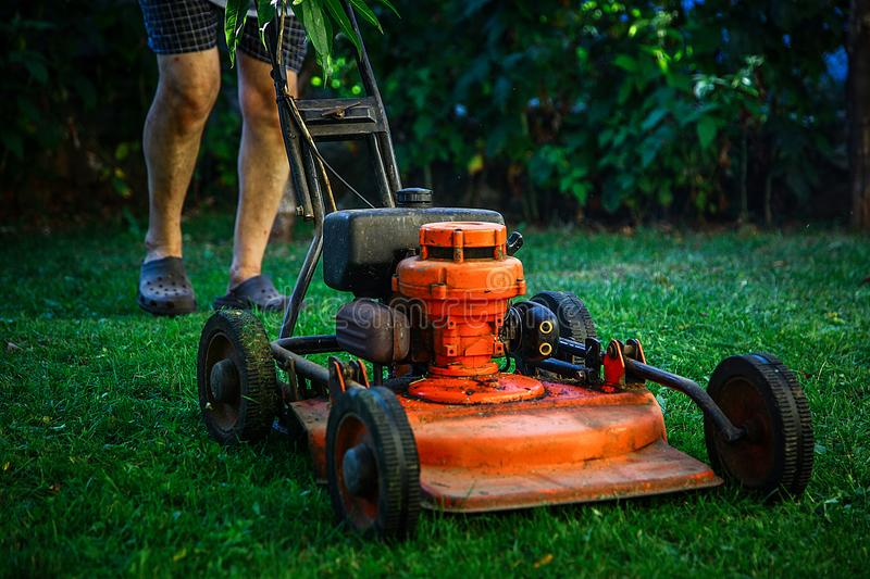 Lawn mowing - summer lawn mowing. Lawn mowing to cut a grass at my home. The farmer cuts grass in the yard stock photos