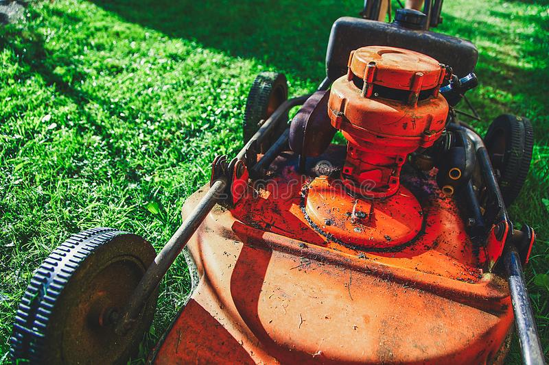 Lawn mowing - summer lawn mowing. Lawn mowing to cut a grass at my home. The farmer cuts grass in the yard royalty free stock photo