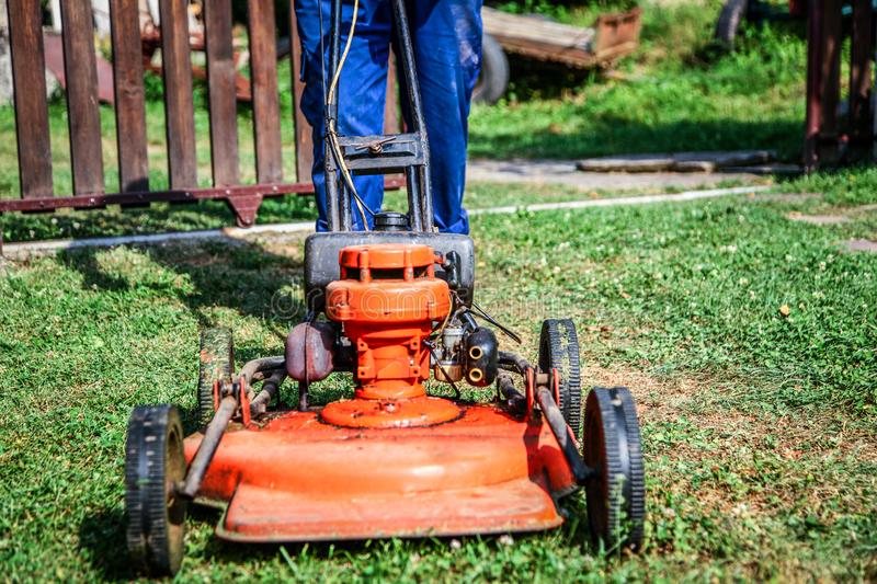 Lawn mowing - summer lawn mowing. Lawn mowing to cut a grass at my home. The farmer cuts grass in the yard royalty free stock photos