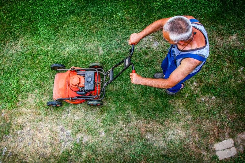 Lawn mowing - summer lawn mowing. Lawn mowing to cut a grass at my home. The farmer cuts grass in the yard royalty free stock photography