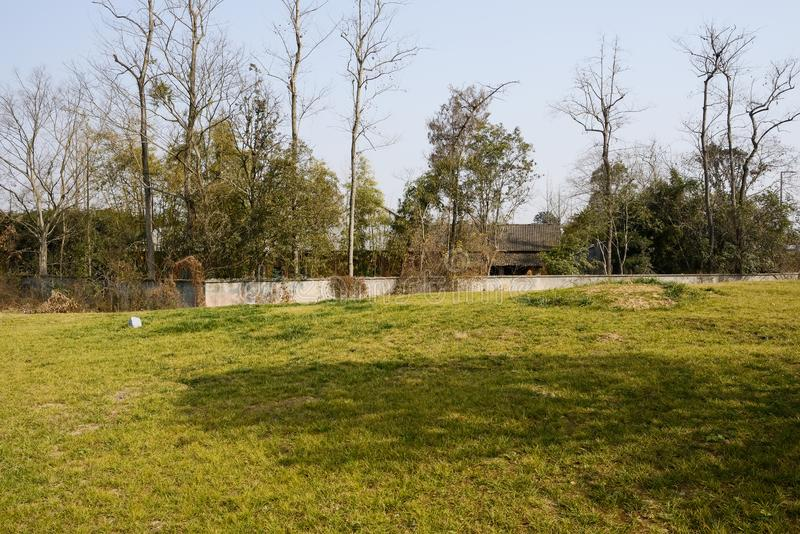 Lawn outside enclosed hut with asbestos shingles in sunny winter. Grassy lawn outside enclosed hut with asbestos shingles in sunny winter afternoon,Chengdu,China stock photography