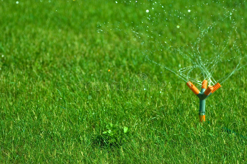 Lawn sprinkler. Spraying water over green grass at night royalty free stock photography