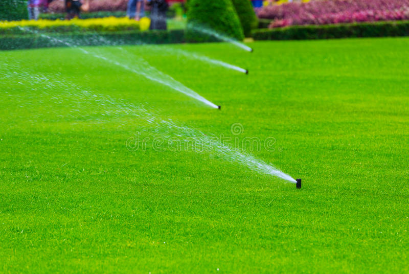 Lawn sprinkler spaying water over green grass. Irrigation system royalty free stock photography
