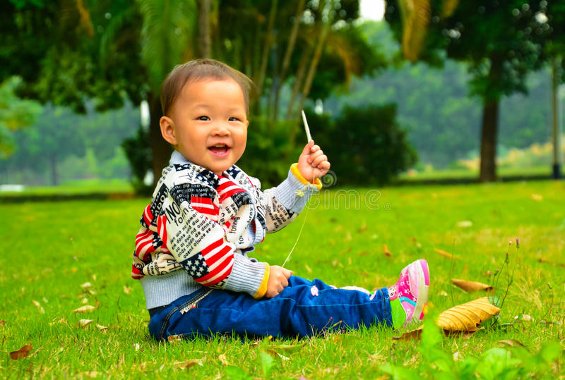 The lawn to entertain the girl(Asia, China, Chinese). Parents don't every moment of every day to take care of their children, and to leave them alone, to stock photos