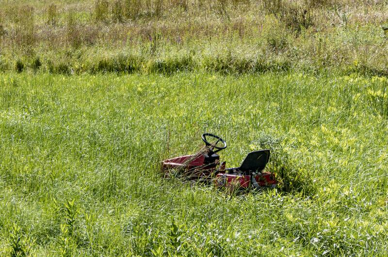 Lawn tractor on overgrown grass royalty free stock image