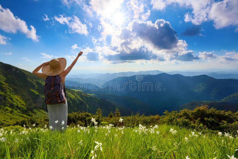 On the lawn of white flowers the hipster girl with back sack stays enjoying the sunset. Summer landscape. stock photos