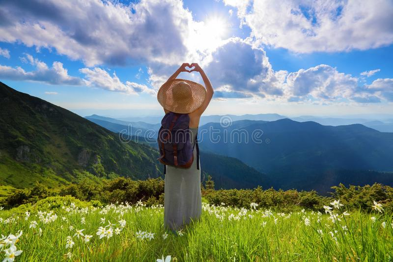 On the lawn of white flowers the hipster girl is staying in long dress, straw hat with back sack, enjoying the sunset. stock image