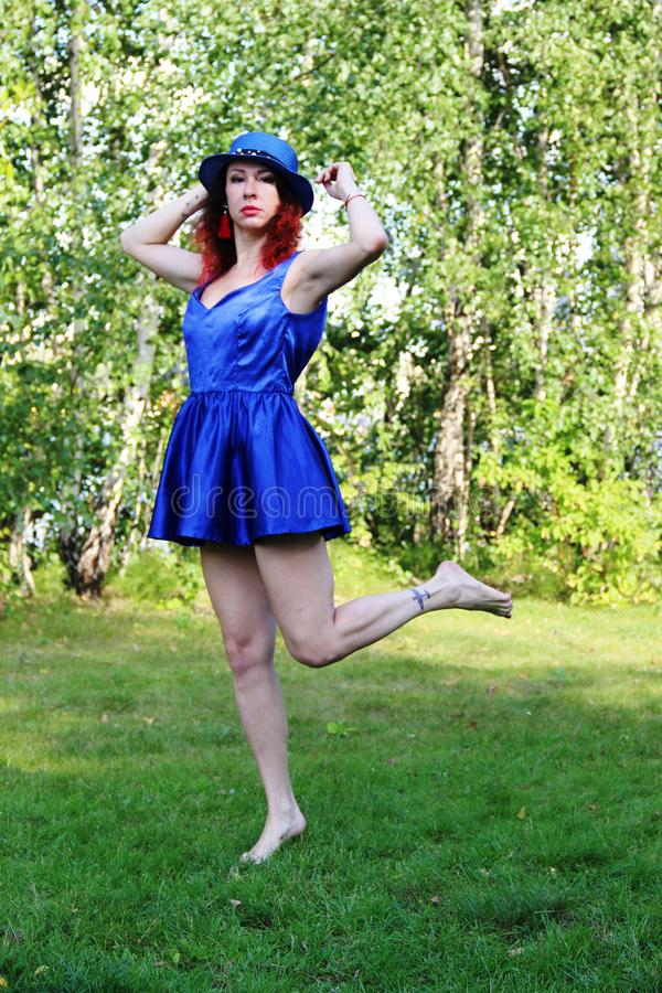 Woman on the lawn with red curly hair in a blue hat and short blue mini dress. Holding a hat. stands on one leg. royalty free stock image