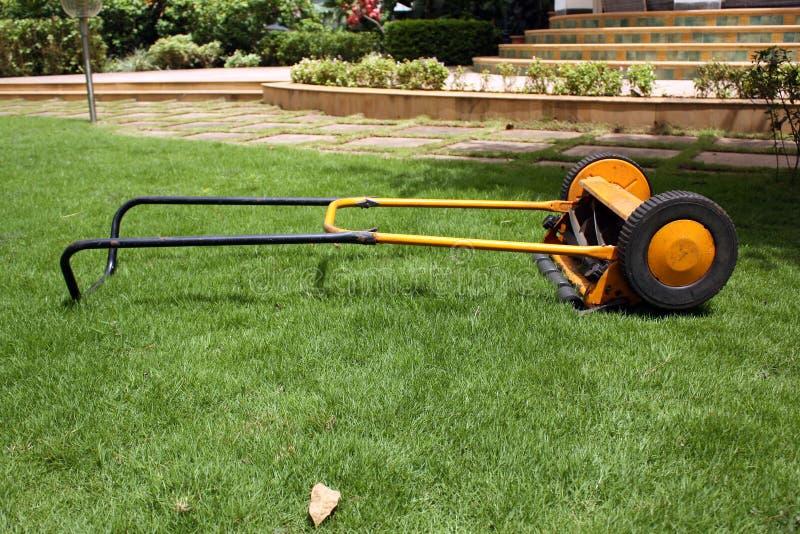 Lawnmower. A bright yellow lawnmower machine on a green garden lawn stock photo