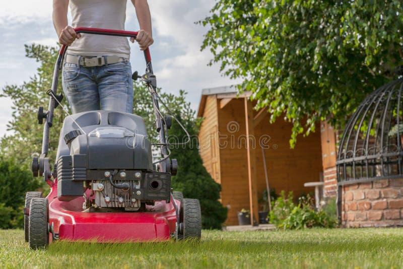 Lawnmower conduzido por um jardineiro fêmea anônimo imagem de stock royalty free