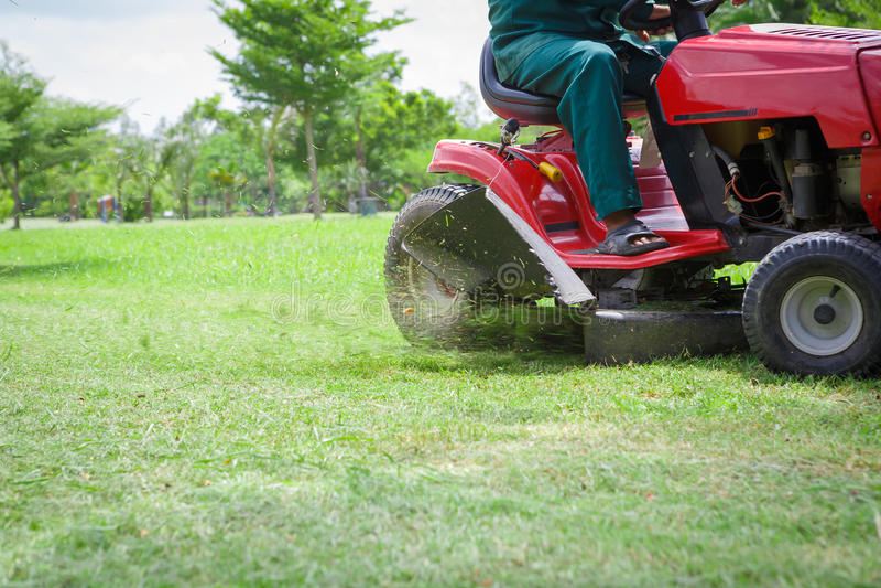 Lawnmower que corta a grama overgrown foto de stock