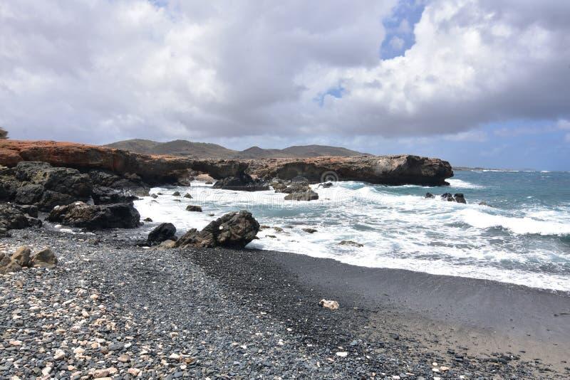 Lawowe skały Graniczy strony Czarna piaska kamienia plaża zdjęcie royalty free
