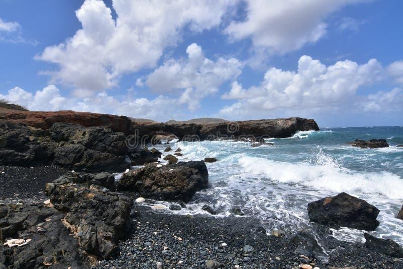 Lawowe skały Wykłada Czarną kamień plażę w Aruba zdjęcie royalty free
