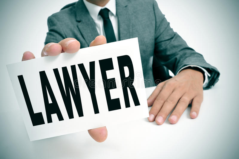 Lawyer. A man wearing a suit sitting in a desk holding a signboard with the word lawyer written in it royalty free stock image