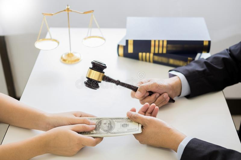 Lawyer being offered receiving money as bribe from client at desk in courtroom.  royalty free stock photos
