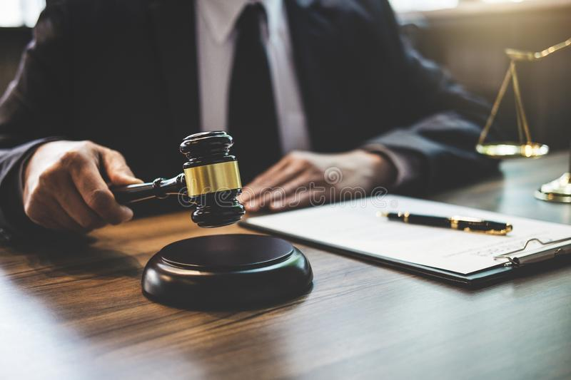 Lawyer or counselor working on a documents and holding gavel in. Courtroom, Justice and Law concept royalty free stock photos