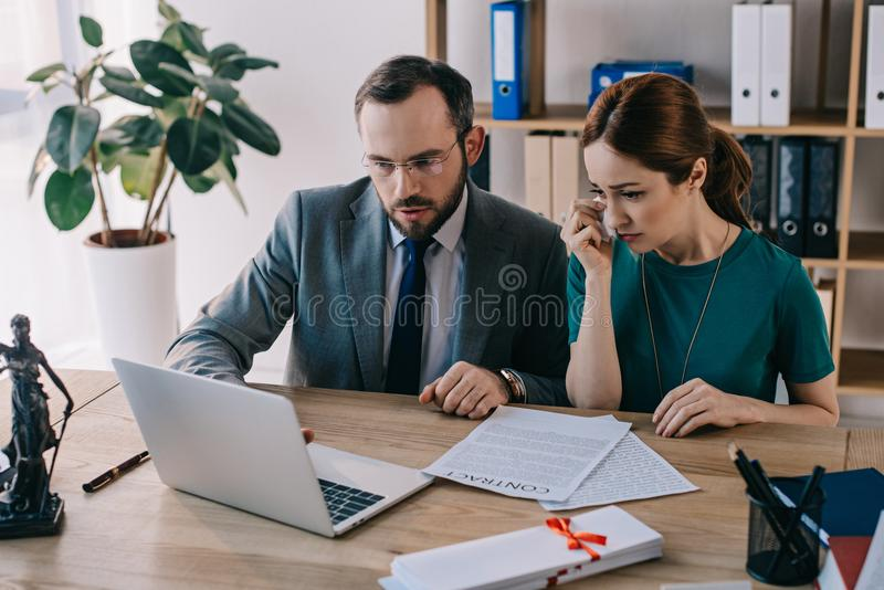 lawyer and crying client discussing contract at workplace with laptop royalty free stock photos