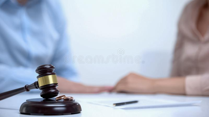 Lawyer gavel and marriage rings lying on background of family couple, closeup stock photography
