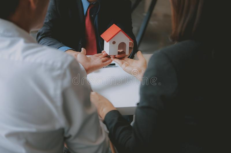 Lawyer insurance broker consulting giving legal advice to couple customer about buying renting house. financial advisor with. Mortgage loan investment contract royalty free stock photo