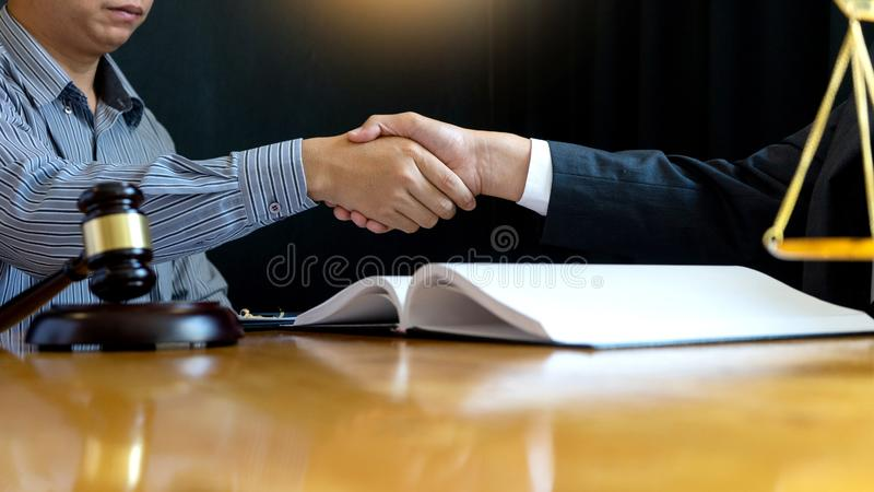 Lawyer or judge gavel with balance handshake. With client or customer about agreement how to use arbitration crop to 16:9 royalty free stock image