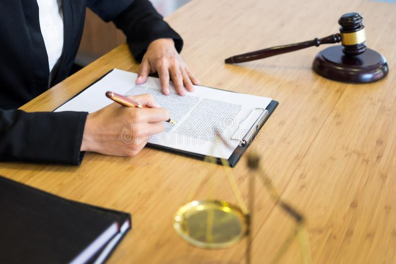 Lawyer judge reading documents at desk in courtroom working on wooden desk background. gavel  golden Weight. and soundblock of. Justice royalty free illustration