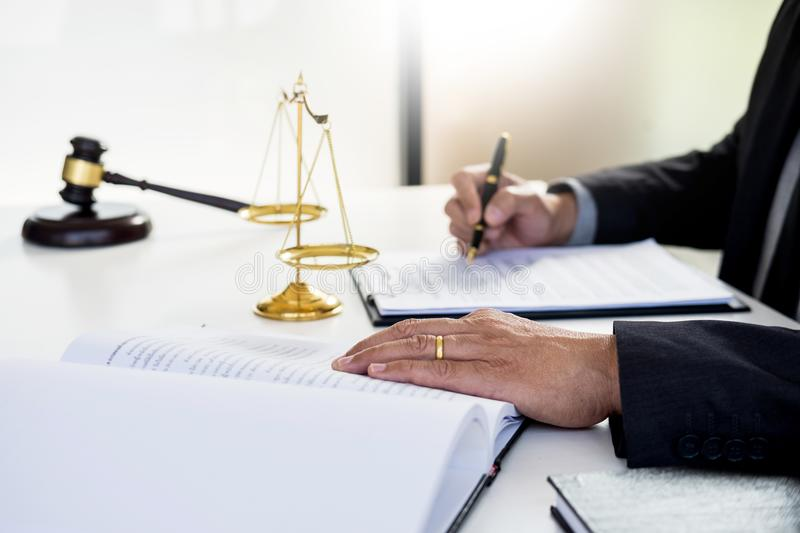 Lawyer judge reading writes the document in court at his desk. Lawyer judge reading and writes the document in court at his desk royalty free stock photography