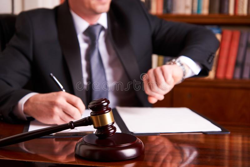 Lawyer or Judge working with agreement. And looks at the clock in Courtroom theme. Justice and Law concept with judge`s gavel on wooden table with law books on stock photo