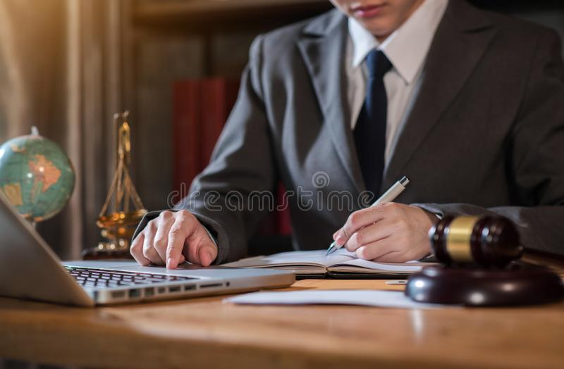 Lawyer office. gavel of Justice with scales and lawyer working on a laptop. stock photography