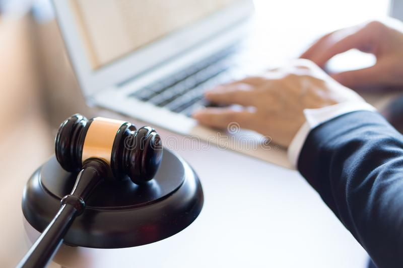 Lawyer office. Judge gavel and lawyer working on a laptop royalty free stock photography