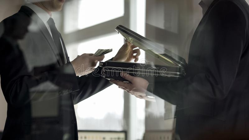 Lawyer opening case and looking at money, concept of illegal job offer, bribe stock photo