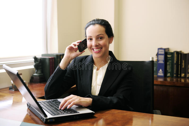 Lawyer on phone with laptop. Female lawyer at office talking on phone and using laptop