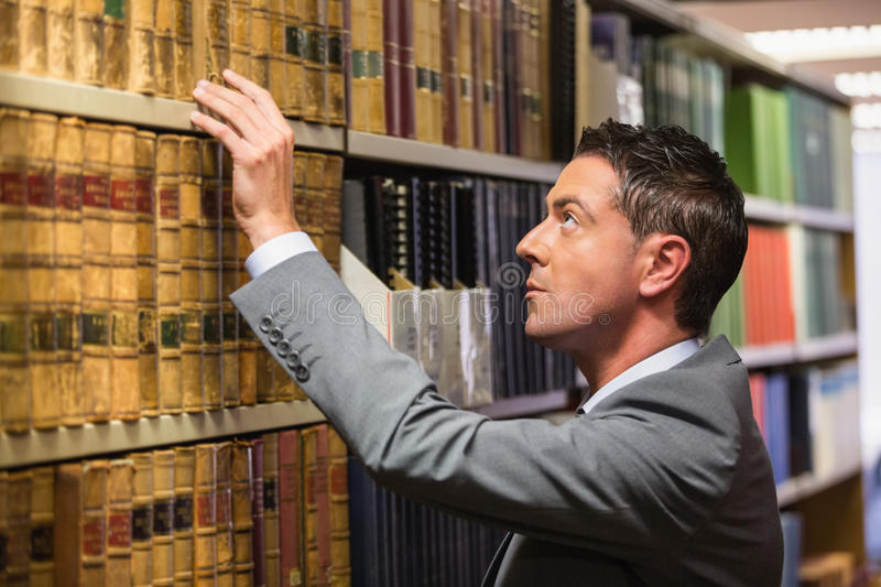 Lawyer picking book in the law library stock images