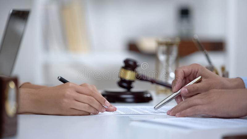 Lawyer showing woman where to sign court claim, professional help to plaintiff stock images