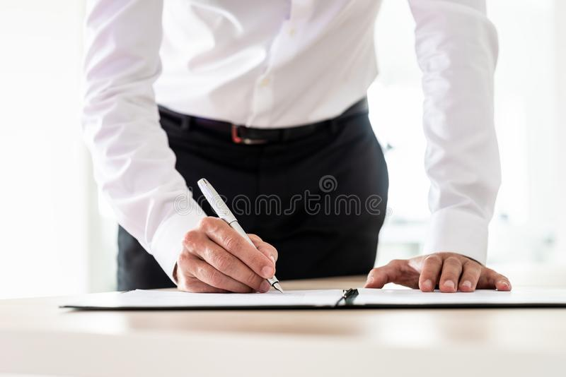 Lawyer signing an important document. In a folder with an ink pen royalty free stock images