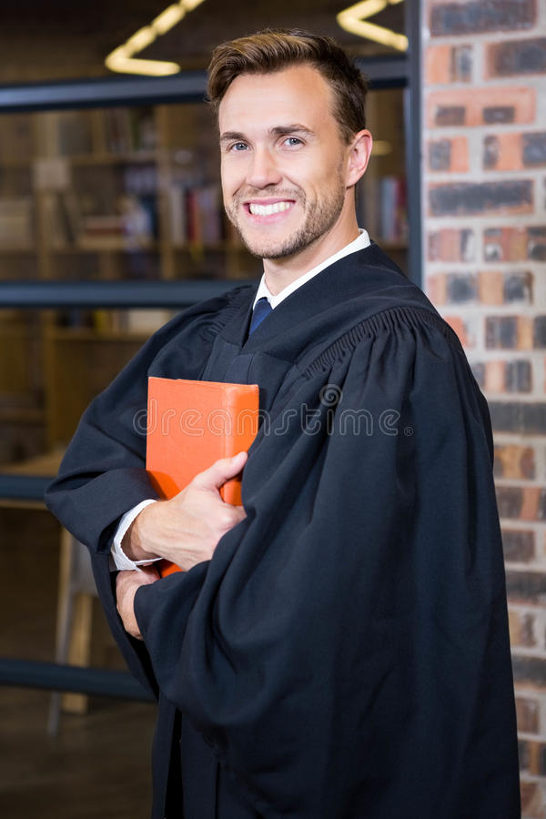 Lawyer standing near library with law book. Portrait of lawyer standing near library with law book in office stock image
