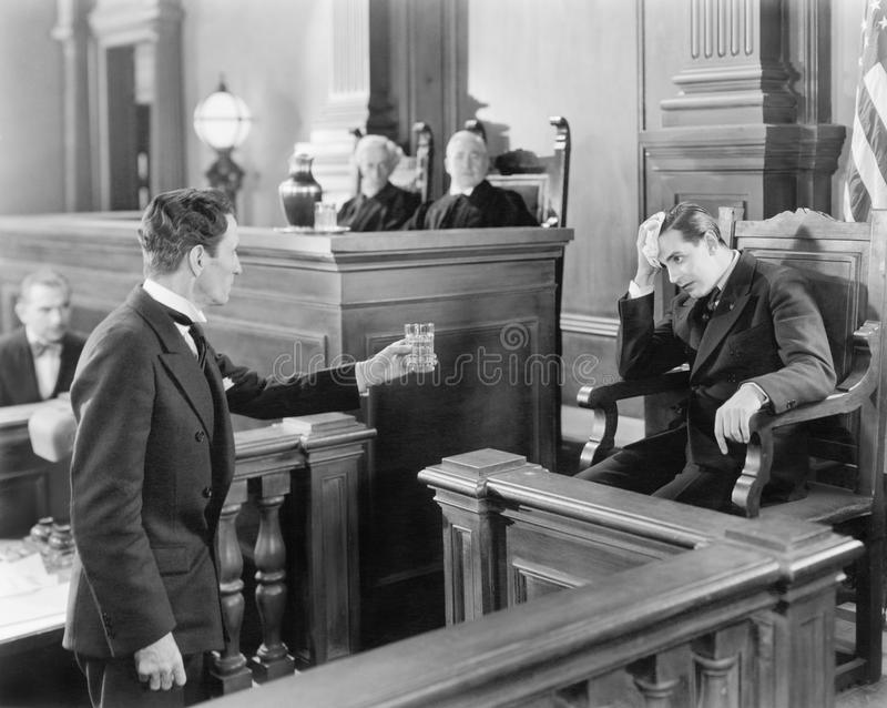 Lawyer and a witness in a courtroom. (All persons depicted are no longer living and no estate exists. Supplier grants that there will be no model release issues stock images