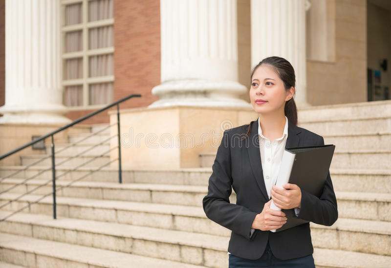 Lawyer woman standing in front of the court. Professional lawyer business woman standing in front of court and holding legal documents waiting for customers royalty free stock photo