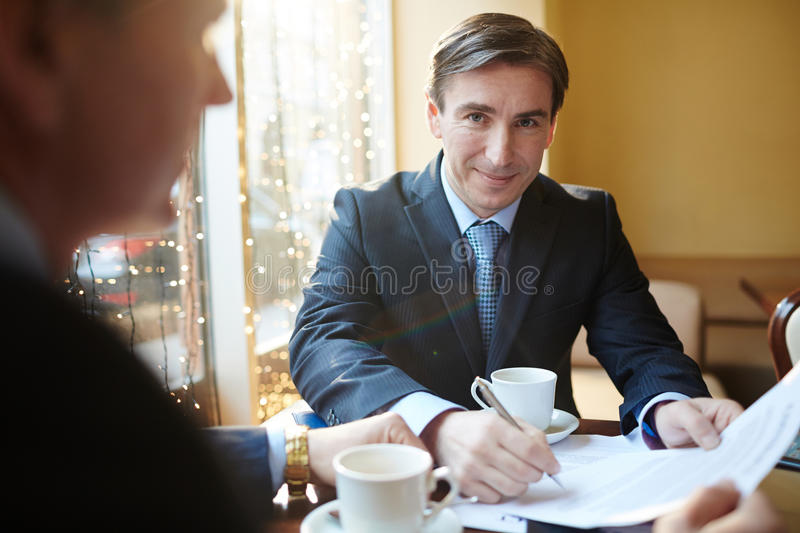 Lawyer at work. Smiling men in formalwear signing financial contract royalty free stock photography