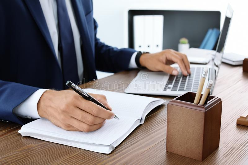 Lawyer working with laptop and notebook at table. Closeup stock photo