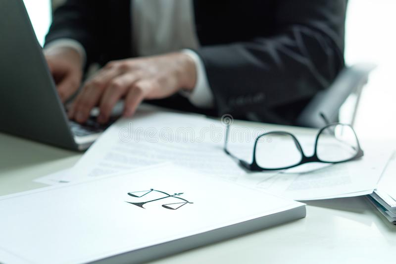 Lawyer working in office. Attorney writing a legal document. Lawyer working in office. Attorney writing a legal document with laptop computer. Glasses on table stock images