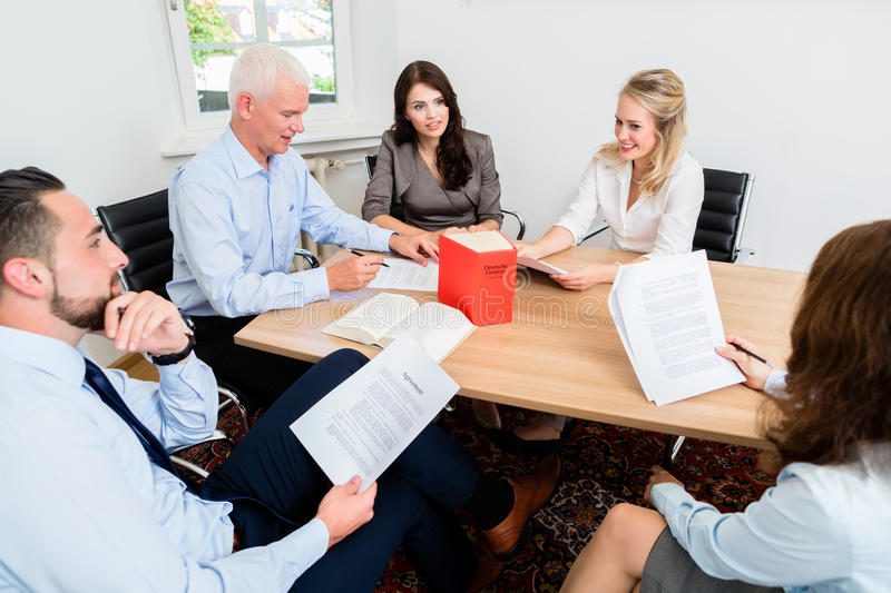 Lawyers in law firm reading documents and agreements. At large conference table royalty free stock image